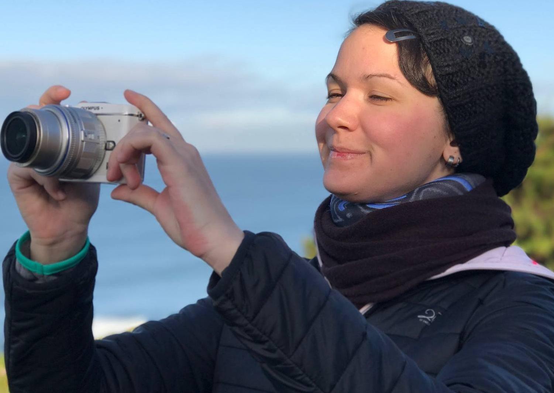 Eine Frau mit Beanie und Halskrause macht Bilder von Fort Funston in San Francisco und lächelt dabei glücklich.