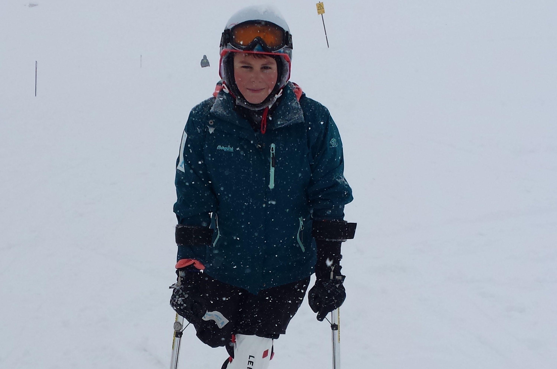 Dieses Bild zeigt Christoph, einen Jungen, auf der Skipiste. Er steht auf einem Ski und hat zwei kleine Ski an den Stecken an den Armen. Er trägt einen Helm, hat rote Wangen und lächelt.