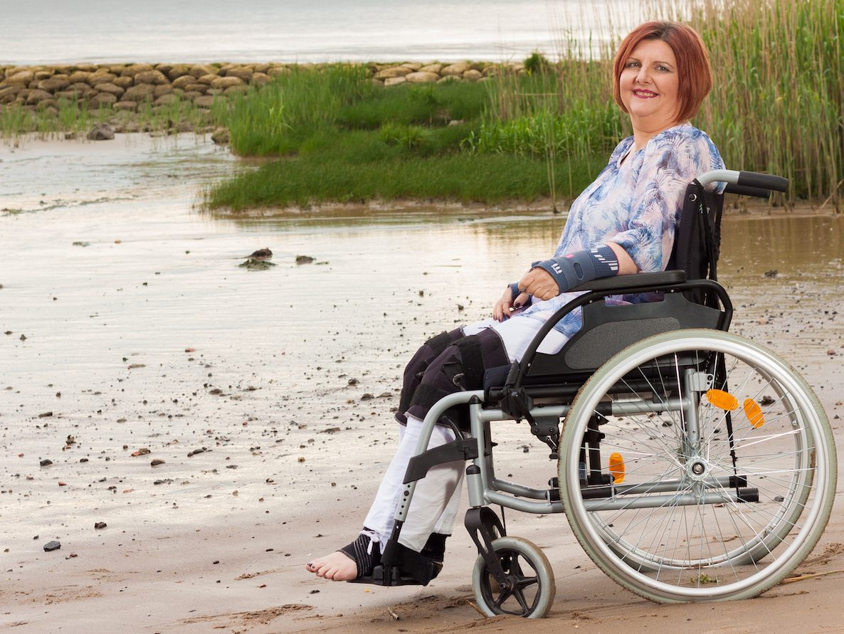 Denise sits in her wheelchair on a beach. She is waring ankle, knee and wrist braces. Also she wears white pants, a blue shirt and red lipstick. Her hair are red and short. In the background is the ocean and some green grass.
