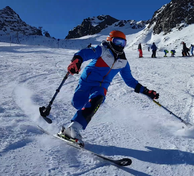 Christoph Glötzner racing down a hill in a blue skiing outfit with a red helmet and a scarf covering his whole face.