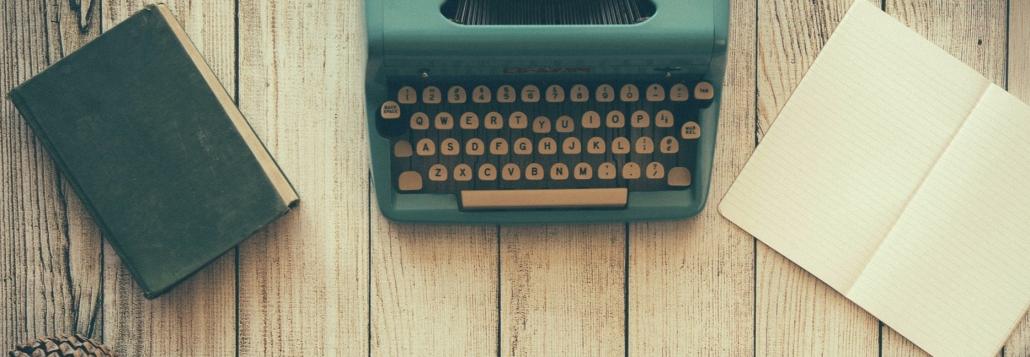 Tisch mit einer Schreibmaschine, einem Notizbuch, einer Brille und einem Buch