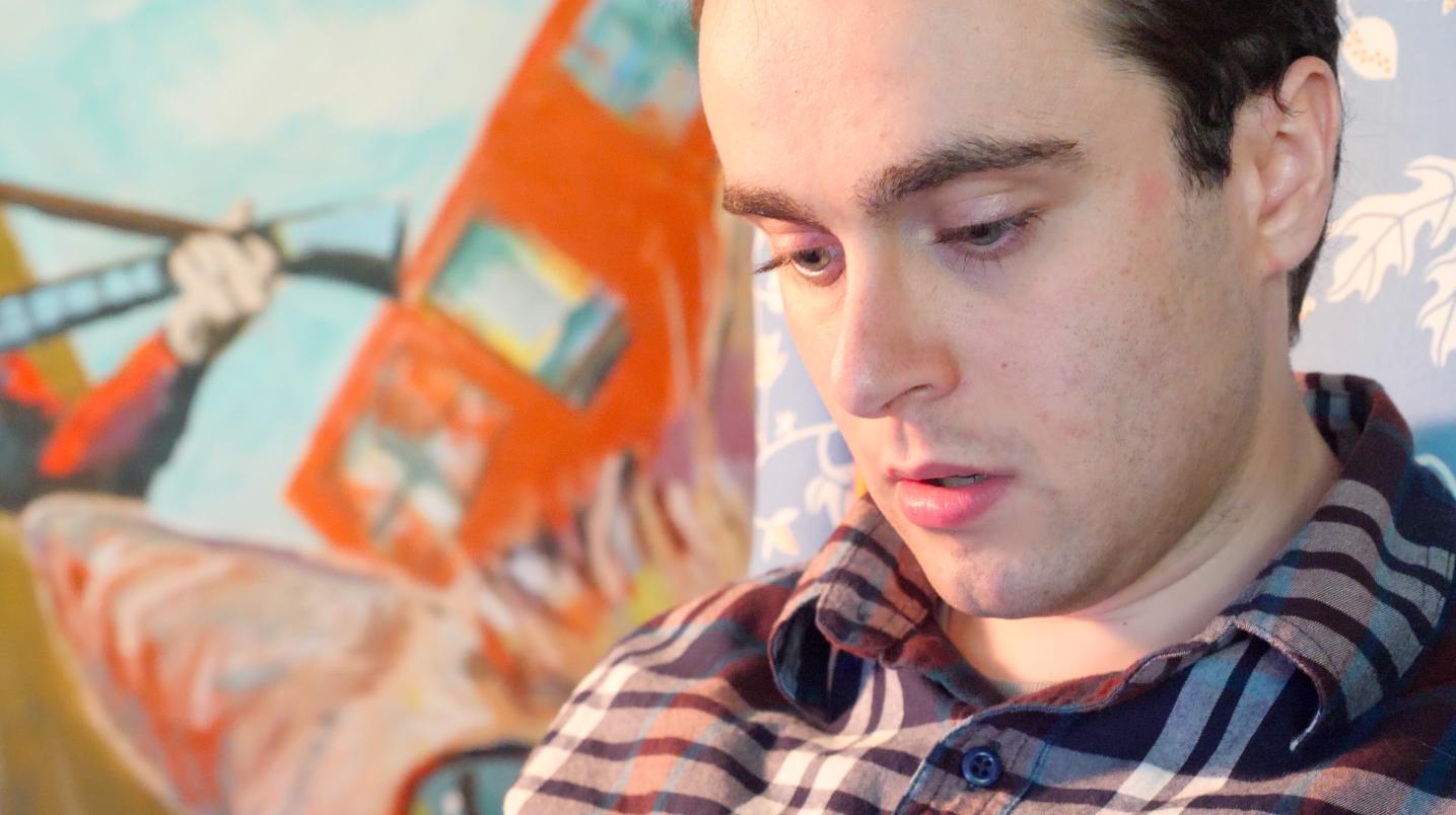 Sam E. Rubin sitzt vor einem Gemälde mit einer Katze und blickt nach unten. Er hat grüne Augen mit langen Wimpern und braune, wellige Haare. Er trägt ein kariertes Hemd.