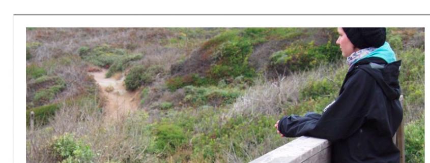 Screenshot: Leading Medicine Guide Blog - Tag der seltenen Erkrankungen - Eine Betroffene erzählt. Auf dem Bild zu sehen ist eine Frau mit schwarzer Beanie Mütze und schwarzer Jacke, die auch einer Brücke steht und in die Natur schaut