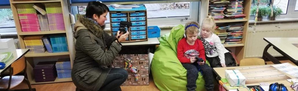 Eine Frau mit kurzen, braunen Haaren und Winterjacke filmt zwei Kinder in einer Schule. Beide Kinder sitzen auf einem grünen Sitzsack und hören ein Hörbuch. Lucas, ein 6-jähriger Junge hat Kopfhörer auf, Lotte, ein 5-jähriges Mädchen mit langen blonden Haaren schaut Aufmerksam ihrem Bruder zu.