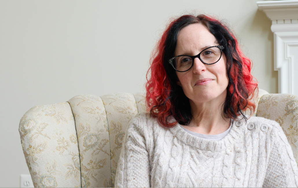 Mid-size front shot of a woman with shoulder-long black and red hair and black, sparkly glasses.