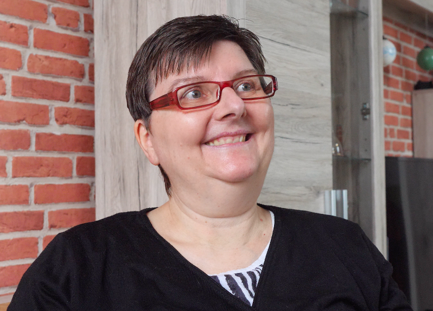 Mid-size shot of a woman with short brown hair and red glasses. She is smiling.