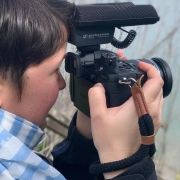 Side view of a woman with short, brown hair holding a camera with a big microphone in front of her face and filming out to the ocean.