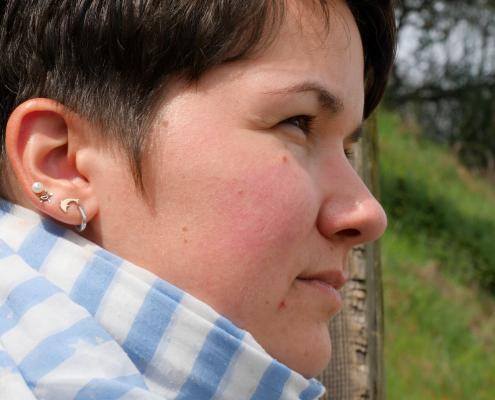 Karina, eine Frau mit kurzen, braunen Haaren schaut in die Ferne. Sie sitzt auf einer Treppe in der Natur und ist im Profil zu sehen. Sie trägt vier Ohrringe. Davon ein Delfin und eine Schildkröte und einen blau, weiß gestreiften Schal.