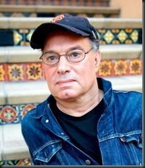 Ein Mann, der ein schwarzes Cap und eine Brille trägt, sitzt auf Stufen