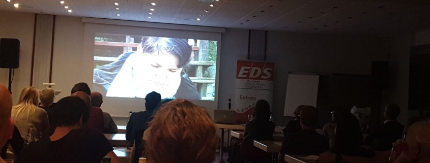 Filmed from the end of a room. In front of the room is a large screen showing 'We Are Visible', Karina's film about Ehlers-Danlos syndrome.