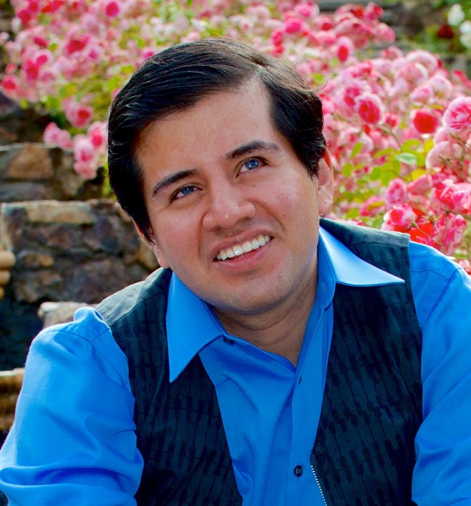Belo Cipriani: Ein Mann mit kurzen, braunen Haaren sitzt auf steinernen Stufen vor pinken Blumen, schaut in die Ferne und lächelt.