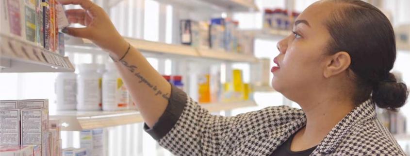 Cassandra, eine Frau mit langen, schwarzen haaren, die zusammen gebunden sind, kauft in einer Apotheke ein
